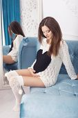 Beautiful Brunette Woman On A 7Th Month Pregnancy In White Sweater. Light Interior. Blue Sofa