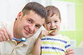 father and kid brushing teeth in bathroom