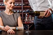 stock photo of wine cellar  - Sommelier pouring wine to the glass with woman in the cellar. Wine degustation