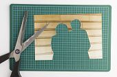 Photograph With Cut Out People With Scissors On Green Cutting Mat