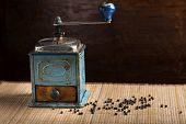 picture of wooden box from coffee mill  - Vintage pepper grinder with pepper on wooden background - JPG