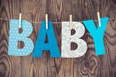 image of clotheslines  - letters of word baby hanging on clothesline against wooden background - JPG