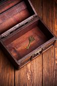 foto of treasure chest  - vintage key inside old treasure chest on wooden background - JPG