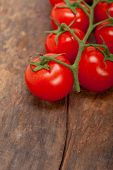 stock photo of cluster  - fresh cherry tomatoes on a cluster over rustic wood table - JPG