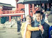 stock photo of shogun  - man holding his daughter during a rainy day in tokyo - JPG