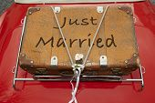 picture of married  - Just Married written on a suitcase placed on the trunk of a red car - JPG