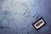 picture of magnetic tape  - audio cassette with magnetic tape in shape of heart on grunge background - JPG