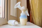 picture of  breasts  - Breast pump and bottle of milk on the windowsill - JPG