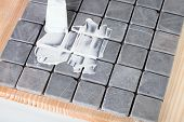 picture of grout  - worker applies grout at grey tiles on a table - JPG