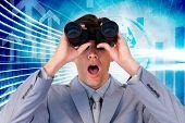 foto of binoculars  - Suprised businessman looking through binoculars against arrow graphics in blue and white - JPG