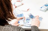 foto of payday  - Successful business woman is counting money bills ona a desk - JPG