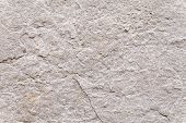 picture of spatial  - Rough surface texture of a weathered block of stone set into the exterior wall of an ancient building - JPG