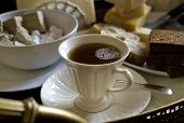 pic of time-piece  - Hot tea in a white porcelain cup cuttlery around it laid on a table - JPG