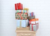 stock photo of stool  - Pile of present boxes on stool on brick wall background - JPG