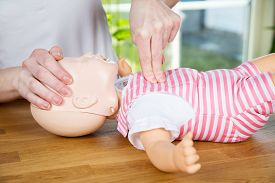 stock photo of baby doll  - woman performing CPR on baby training doll with one hand compression - JPG