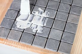 pic of grout  - worker applies grout at grey tiles on a table - JPG