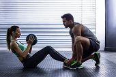 Side view of a muscular couple doing abdominal ball exercise poster
