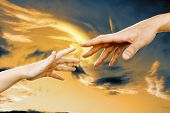 image of father child  - hand the child and hand the men against the sunset sky - JPG