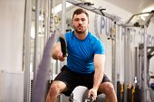 stock photo of battle  - Young man working out with battle ropes at a gym - JPG
