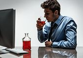 stock photo of alcoholic drinks  - Young alcoholic man drinking whiskey sitting drunk at office with computer  - JPG