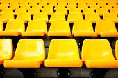 stock photo of bleachers  - Plenty of yellow plastic seats at stadium - JPG