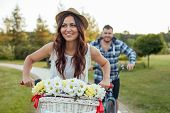 stock photo of she-male  - Cheerful loving couple is cycling with pleasure. The woman is outdriving her man. She is looking aside with pleasure. They are smiling ** Note: Soft Focus at 100%, best at smaller sizes - JPG
