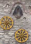 picture of wagon wheel  - Old Antique Wagon Wheels Harness adn Horseshoe on Limestone Background - JPG