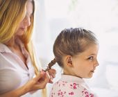 Постер, плакат: Mother Hairdressing Her Preteen Daughter At Home