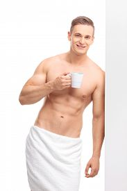 stock photo of mug shot  - Vertical shot of a young handsome man holding a coffee mug and leaning against a wall isolated on white background - JPG