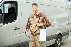 stock photo of pesticide  - Young Male Worker With Pesticide Standing Near The Van - JPG