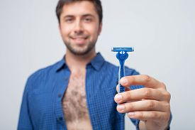 picture of razor  - Cheerful guy is showing a razor to the camera - JPG