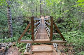 stock photo of suspension  - Suspension Bridge Over Falls Creek in Gifford Pinchot National Forest Hiking Trail in Washington State Front View - JPG