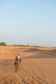 stock photo of sahara desert  - A couple of tourist ride camel into Sahara desert as Desert Tour on March 18 2014 in Merzouga city Morocco - JPG