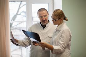 stock photo of professor  - Professor and young female doctor examining and comparing two x - JPG