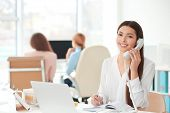 Beautiful young woman talking by telephone while working in office poster