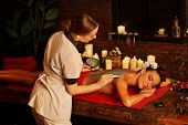 Mud mask of woman in spa salon. Back massage with clay full body . Girl on interior with candles in  poster