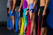 Athletes exercising with resistance band in gym poster