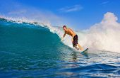 Attractive Male Surfer Rides a Large Blue Wave, Perspective from water level