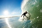 Surfer riding Wave with Sun and Blue Sky