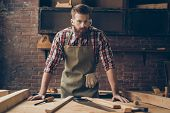 Bearded Handsome Cabinetmaker At The Tabletop With Tools.  Stylish Craftsman With Brutal Hairstyle A poster