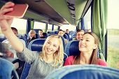 transport, tourism, road trip and people concept - happy young women or friends in travel bus taking poster