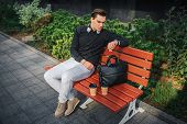 Serious Young Man Sit On Bench Outside And Look At Watches. There Are Two Cups And Black Leather Bag poster