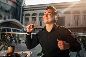 Happy Young Man Enjoys Listening To Music. He Dance At Table Outside. Guy Wave With Hands. It Is Sun poster