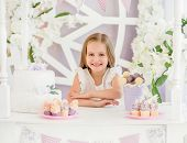Little cute blond girl holding a sweet cake on the background of pretty decorated candy bar poster