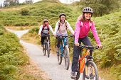 Pre-teen girl riding mountain bike with her parents during a family camping trip, close up poster