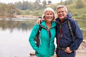 Happy senior couple standing on the shore of a lake smiling to camera, Lake District, UK poster