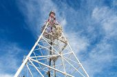 Telecommunication tower with antennas against blue sky background