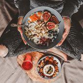 Woman In Woolen Sweater And Jeans Eating Vegan Rice Coconut Porridge With Figs, Berries, Nuts. Healt poster