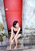 Girl sits in red doorway