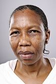 Old African woman looks at camera with sad eyes